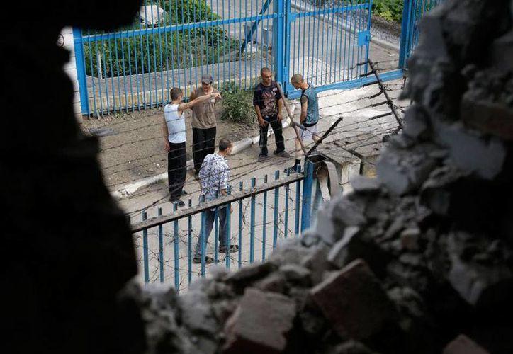 La imagen muestra a los presos de una cárcel de máxima seguridad, a través de un boquetes que dejó el ataque en Donetsk, Ucrania. (AP)