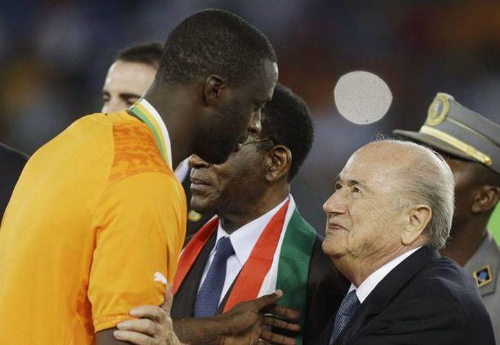 Joseph Blatter (der.), actual presidente de la FIFA, se enfrentará a Luis Figo y Ali bin al-Hussein, en el proceso electivo. En la imagen, de archivo, Blatter saluda a Yayá Touré. (AP)