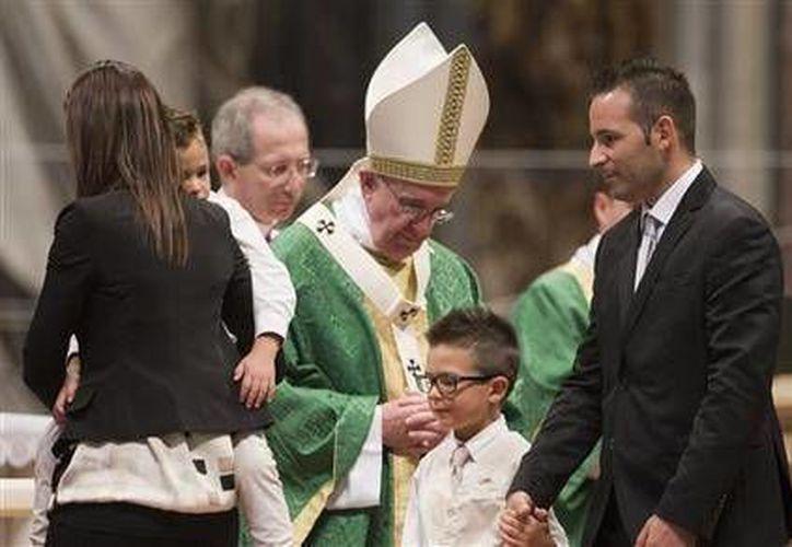 Una familia tras entregar ofrendas al papa Francisco durante la misa que abrió el sínodo de obispos. (Agencias)