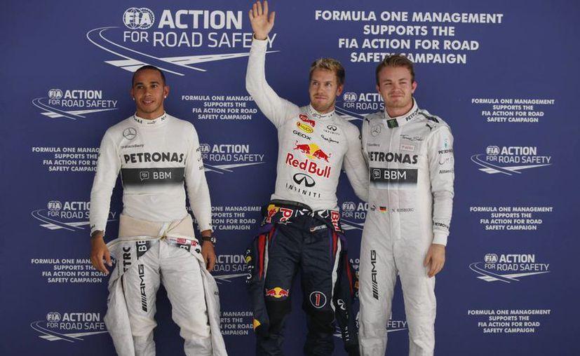 Vettel, flanqueado por Nico Rosberg (d) y Lewis Hamilton, tras la disputa de la pole. (Agencias)