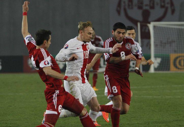 Akaki Khubutia (i) y Murtaz Daushvili, de Georgia, disputan el balón contra el polaco Sebastian Mila, quien anotó uno de los goles en la abultada victoria de su selección en partido de eliminatorias rumbo a la Eurocopa. (Foto: AP)