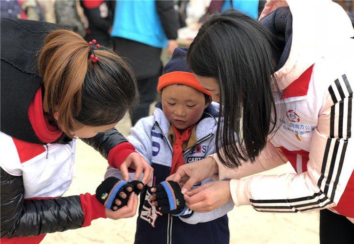 Los voluntarios ayudan a Wang Fuman a ponerse un par de guantes. (Foto: Ye Longfei)