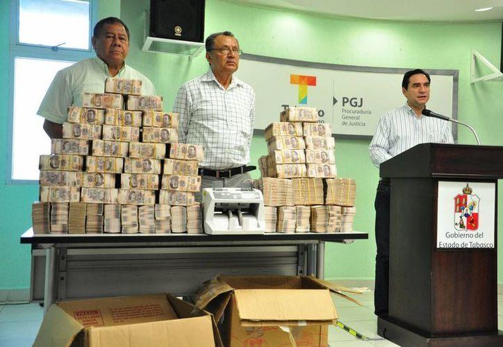 El notario (al centro) apareció en la rueda de prensa en la que se mostró el dinero que se decomisó en un rancho del extesorero de Granier. (Archivo/Notimex)