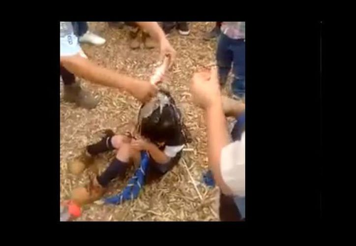 Usuarios de redes sociales condenaron el video donde también se observa como la menor comienza a llorar en el momento en que es bañada con refresco. (Captura de pantalla)