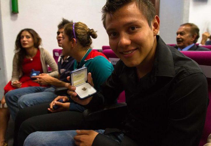 El clavadista Germán Sánchez muestra el Pin Olímpico que recibió por ser medallista de oro en los Juegos Olímpicos Londres 2012. (Notimex)