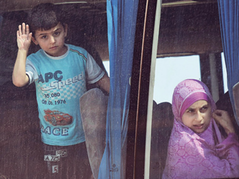 Syrian kids who were held with their families for years by al-Qaida-linked fighters, look through a bus window upon their arrival at a government-controlled checkpoint, near Aleppo, Syria. (AP)