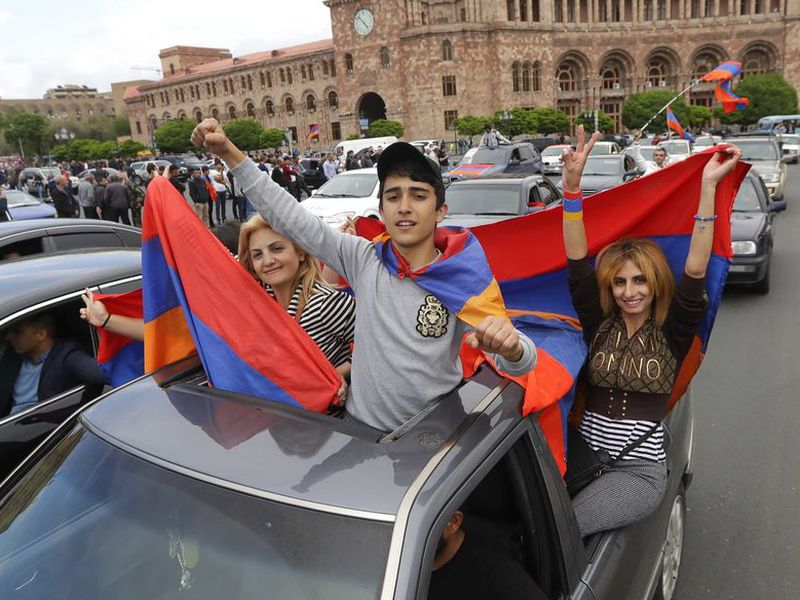 Protesters hold Armenian national flags as they gather at Republic Square in Yerevan, Armenia. (AP)