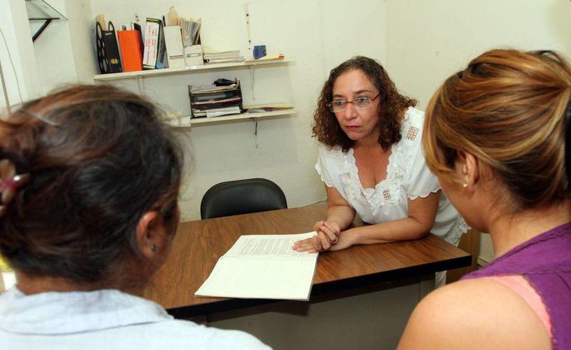 En la imagen, una funcionara del IMM mientras atiende a un par de mujeres que sufren violencia doméstica. (Milenio Novedades)