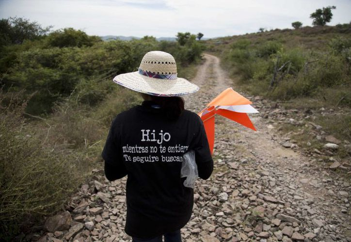 """Una mujer con una camiseta en la que puede leerse """"Hijo, mientras no te entierre te seguiré buscando"""", camina por una colina buscando a su familiar en las afueras de Iguala, Guerrero. (Agencias)"""