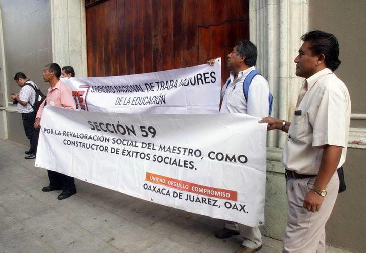 Padres de familia y profesores de la Sección 59 del SNTE protestan al exterior de casa oficial, para exigir una audiencia con el gobernador, Gabino Cué Monteagudo, luego de las agresiones y amenazas que han recibido por parte de la Sección 22 del SNTE.  (Archivo/Notimex)