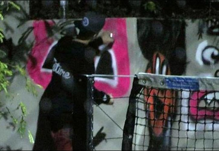 Justin Bieber pintando graffiti en una pared del QT Gold Coast Hotel, en Australia. (Agencias)