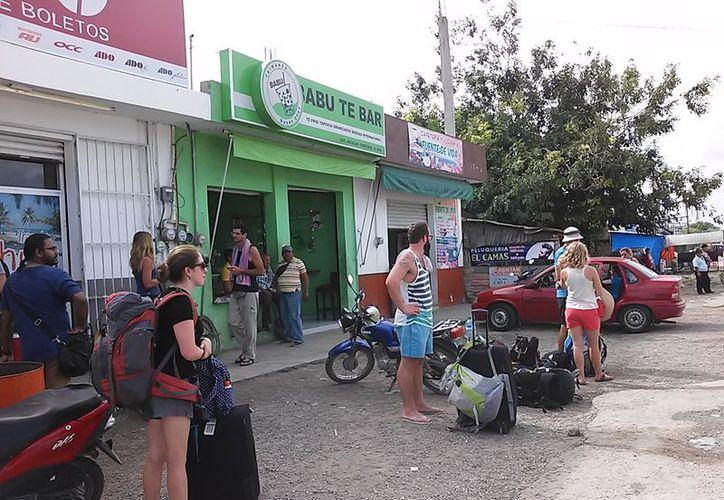 En temporada de vacaciones, es común observar a los turistas esperar su transporte sentados o parados a la intemperie. (Javier Ortiz/SIPSE)