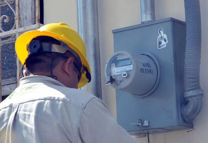 CFE advierte de engaños con mensajes apócrifos de cobro. Imagen de contexto de un trabajador de la CFE mientras checa el medidor de electricidad de un domicilio. (Milenio Novedades)