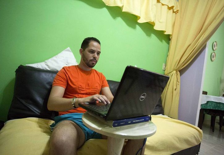 Roberto Carlos Villamar usa su laptop con el nuevo internet experimenntal en la sala de su casa en La Habana, Cuba. (AP/Desmond Boylan)