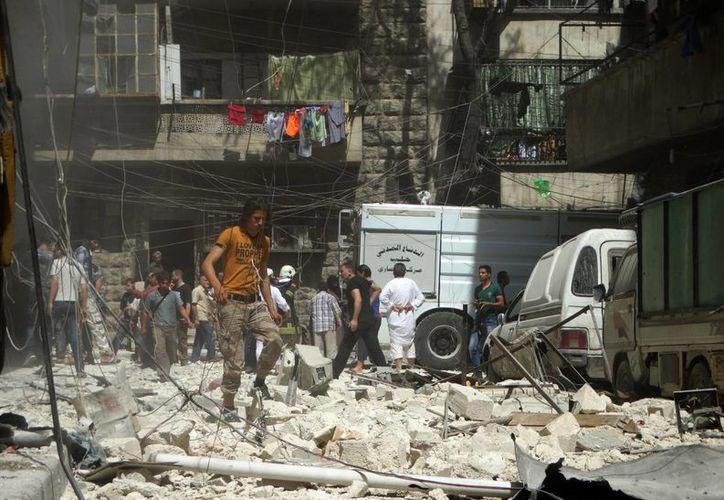 Varias personas comprueban los daños ocasionados por ataques aéreos en el barrio Kalasa de Alepo (Siria), el pasado mes de abril. (EFE)