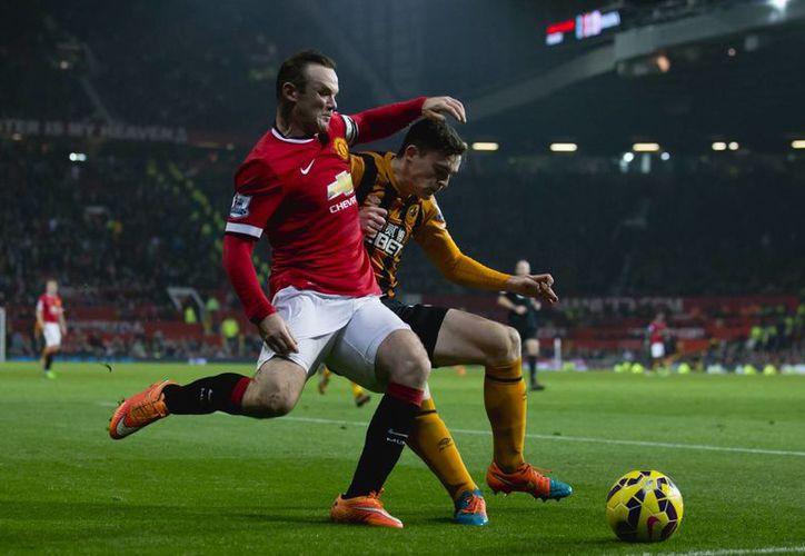 Rooney se dispone a meter un gol en el partido del United ante Hull. En la foto, disputa la redonda con Andrew Robertson. (Foto: AP)