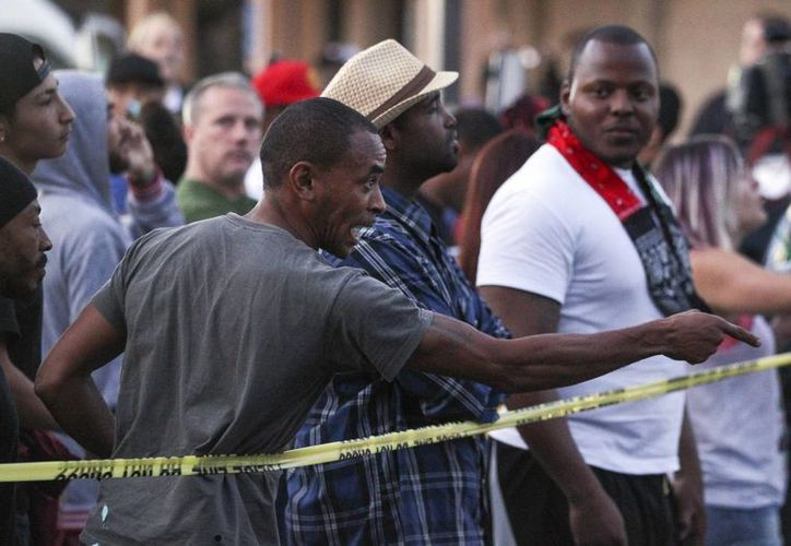 Un hombre le grita a la policía que se encuentra en la escena donde un afroameriocano murió a consecuencia de los disparos que los agentes realizaron en su contra.  (Hayne Palmour IV/The San Diego Union-Tribune vía AP))