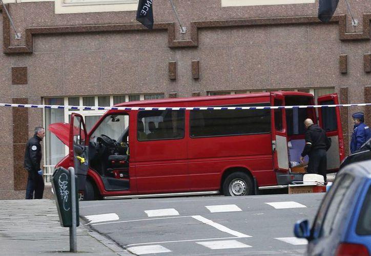 Un vehículo sospechoso, la furgoneta roja que aparece en la foto, es acordonado por la policía cerca del Parlamento Europeo en Bruselas, en la capital belga. (EFE)