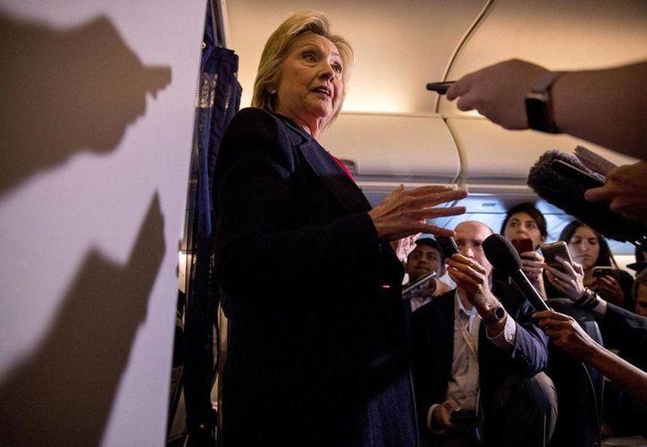 La candidata demócrata Hillary Clinton habla con la prensa durante el vuelo hacia Tampa, Florida, como parte de su campaña. Según sondeo de CNN, Donald Trump ha repuntado y casi están parejos en intención de voto. (Foto: AP/Andrew Harnik)