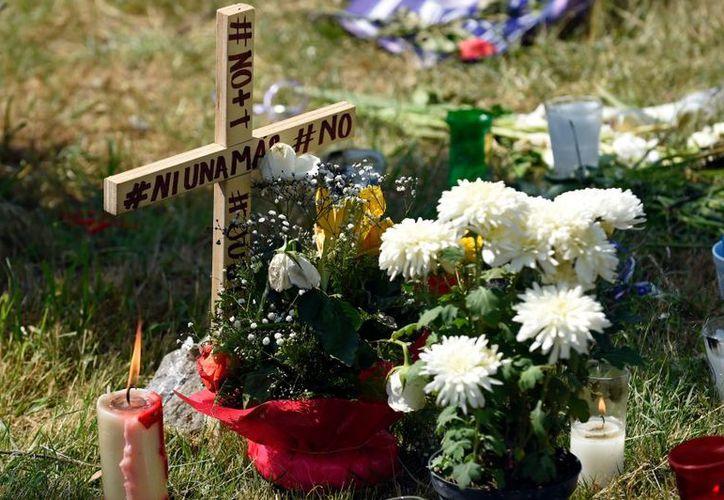 En el lugar donde se hallaron restos de las presuntas víctimas de los feminicidas de Ecatepec, vecinos han colocado flores. (AFP)