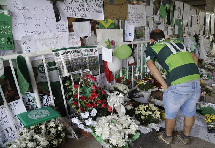 Un fanático del equipo de fútbol Chapecoense lee los mensajes dejados por la gente en el estadio Arena Conda en Chapeco, Brasil. (AP/Andre Penner)