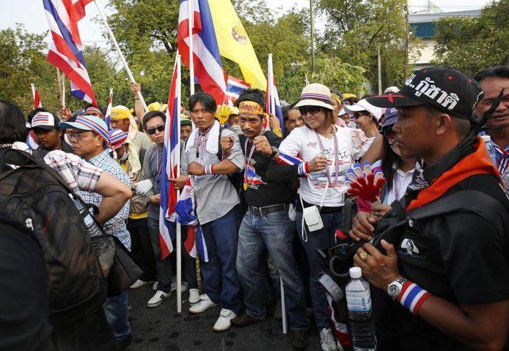 Manifestantes forman una cadena humana a las afueras de la casa de Gobierno de la primera ministra Yingluck Shinawatra, en repudio contra la influencia de su familia. (Agencias)