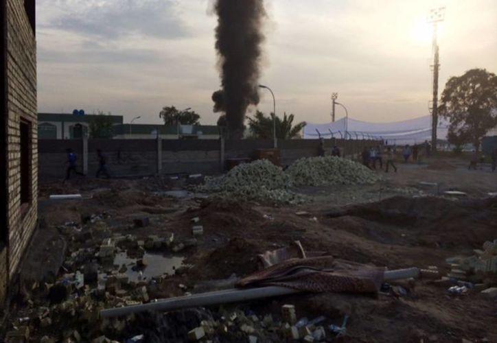 Una columna de humo asciende desde el sitio donde estallaron las bombas que mataron a varias personas durante una reunión proselitista. (Agencias)