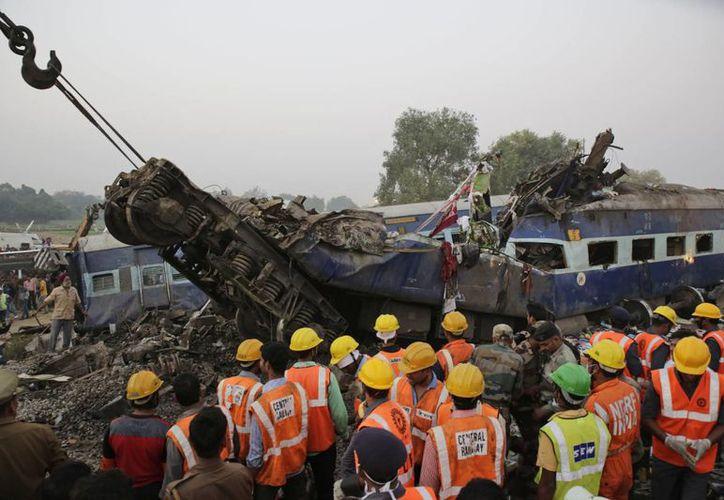 Los rescatistas buscaron en los 14 vagones de un tren de pasajeros, el cual se descarriló cerca del pueblo de Pukhrayan, en el distrito de Kanpur Dehat, estado de Uttar Pradesh, India. (AP/Rajesh Kumar Singh)