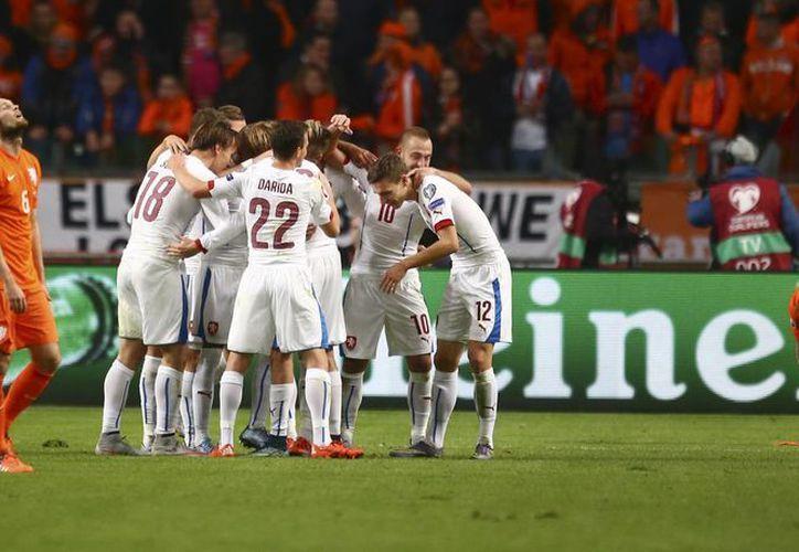 Mientras República Checa celebra al centro del campo su pase al repechaje, dos jugadores de Holanda no dan crédito a su eliminación rumbo a la Eurocopa 2016: Daley Blind (i) y Wesley Sneijder (d). (AP)