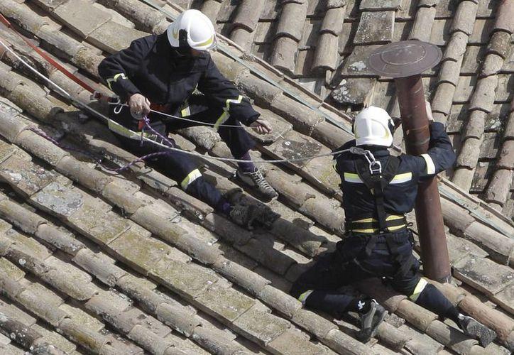 Bomberos hacen ajustes para colocar la parte superior de la chimenea de la Capilla Sixtina. (Agencias)