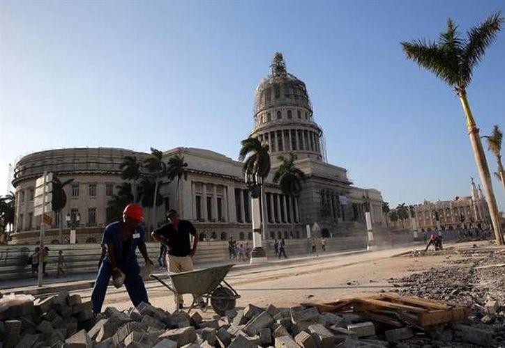 Varios obreros trabajan en la reparación de los alrededores del Capitolio Nacional, uno de los principales puntos que 'reciben una manita de gato' ante la próxima visita del presidente de EU a Cuba. (EFE)