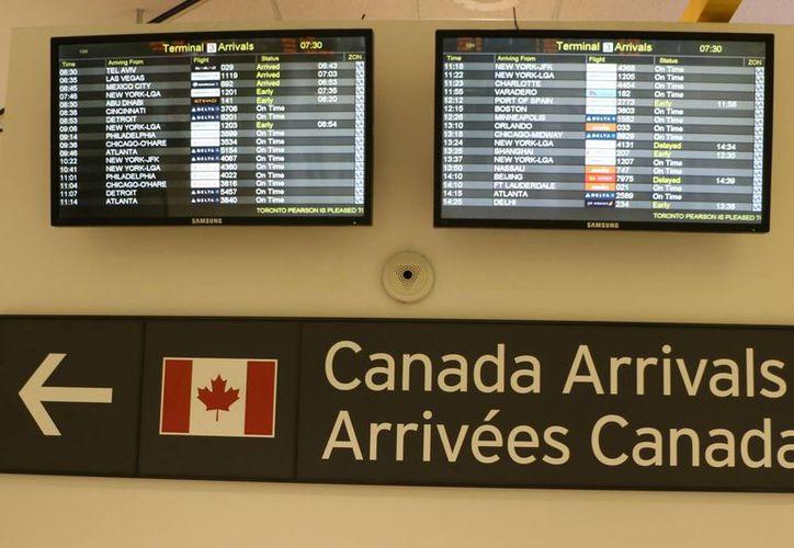 Los mexicanos que tengan visa vigente para viajar a Canadá no requieren visa. Imagen de una de las pantallas del aeropuerto donde se ve la lista de vuelos a ese país. (Notimex)