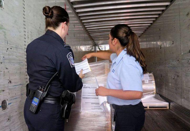 La agente de la Oficina de Aduanas y Protección Fronteriza de EU, Rachael McCormick (izq) y la agente aduanal mexicana Alejandra Galindo inspeccionan de manera conjunta un camión de carga que transporta artículos de México hacia EU en la Instalación de Inspección Mariposa en el puerto de Ingreso en Nogales, Arizona. (AP/Astrid Galván)