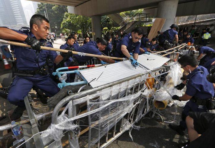 La policía retiró barricadas metálicas de otro campamento de protesta en un camino a la zona de tiendas Causeway Bay para abrir un carril al tráfico. (Agencias)