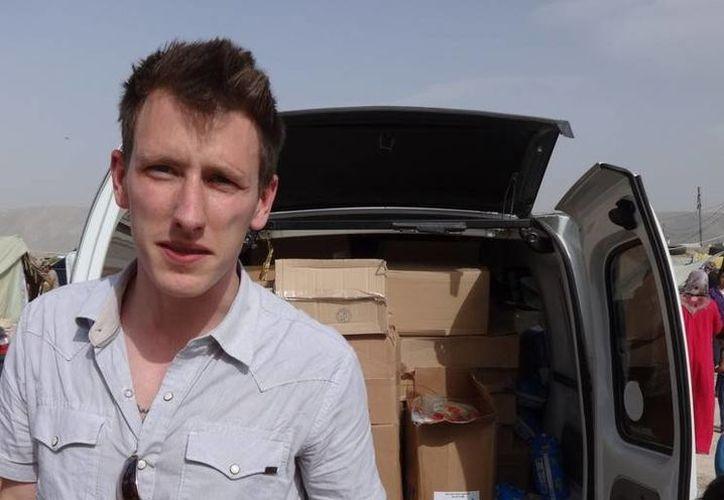 En esta foto sin fecha cedida por por su familia se ve a Peter Kassig distribuyendo suministros a refugiados sirios. (Agencias)
