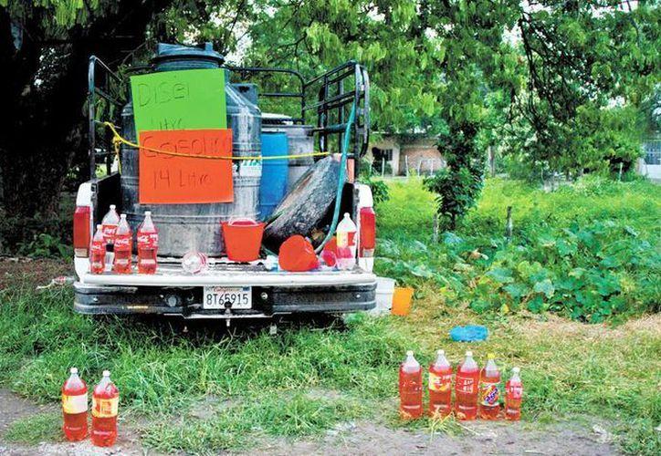 Venta del combustible con sobreprecio en las comunidades afectadas de Michoacán; la escasez ha generado un mercado negro y cambiante a cada día. (Milenio)