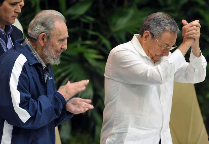 Fidel Castro le sugirió a Obama que 'reflexione y no trate ahora de elaborar teorías sobre la política cubana'. El expresidente cubano (i) aplaude a su hermano, Raúl (d). (Imagen de archivo de AFP)