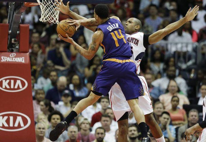 Gerald Green, de Suns, intenta anotar pero tiene enfrente a Al Horford, de Hawks, que ganó e impuso un récord de victorias de la franquicia en la NBA. (Foto: AP)