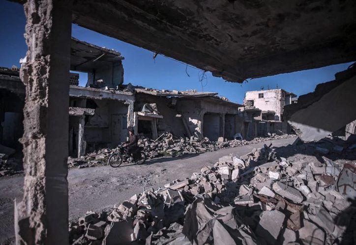 Un hombre circulaba este lunes en moto por las calles destruidas de Duma, en las afueras de Damasco, Siria. (EFE)
