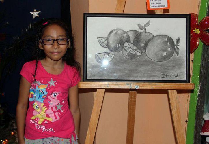 La pequeña artista Itzel López compartió una de sus pinturas y admitió que una de la técnica de carboncillo la divierte mucho. (Tomás Álvarez/SIPSE)