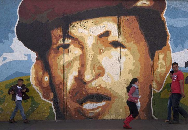 Venezolanos caminan frente a un mural con el rostro de su presidente, en Caracas. (Agencias)