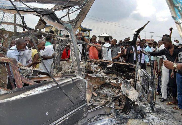 Unos civiles se acercan a los restos de un autobús carbonizado tras la explosión de una bomba en Port Harcourt, Nigeria. (EFE)