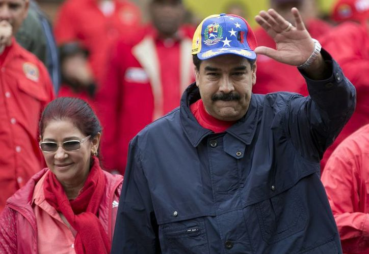 El presidente venezolano Nicolás Maduro saluda a partidarios, acompañado de su esposa Cilia Flores, durante una marcha por el Día del Trabajo, en Caracas, Venezuela, el 1 de mayo de 2016. (Foto AP/Ariana Cubillos, archivo)