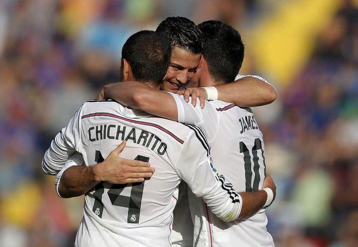 Javier Hernández se funde en un abrazo con Cristiano Ronaldo, uno de los mejores jugadores del mundo, y James Rodríguez, goleador del Mundial de Brasil. (EFE)