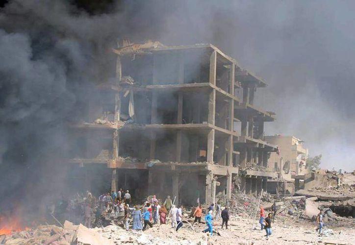 Fotografía facilitada por la Agencia Oficial de Noticias siria, SANA, que muestra hoy a varias personas en el lugar donde explosionó una bomba en Qameshli, Siria. (EFE)