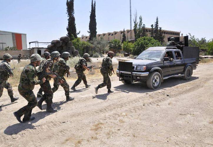 Efectivos leales al presidente Bashar Assad se apostan durante enfrentamientos con rebeldes sirios en Alepo, Siria. (Agencias)