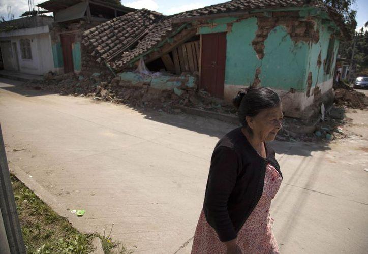 Una mujer pasa frente a una casa destruida por el terremoto de 7.4 del miércoles en el poblado de San Marcos, Guatemala. (Agencias)