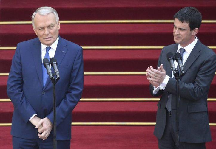 Manuel Valls (der), aplaude al saliente primer ministro francés Jean-Marc Ayrault después de la ceremonia de toma de posesión. (Agencias)