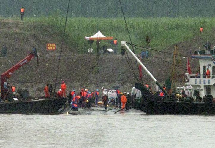 Trabajadores sanitarios (de blanco) esperan los cadáveres mientras rescatistas (de naranja) trabajan en el barco hundido en el río Yangtsé en el centro de China. (Foto AP/Andy Wong)
