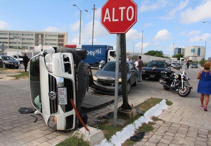 La guiadora de un Bora se distrajo y después de volarse un alto en Altabrisa fue chocada y su auto volcó. (Fotos: Aldo Pallota/SIPSE)